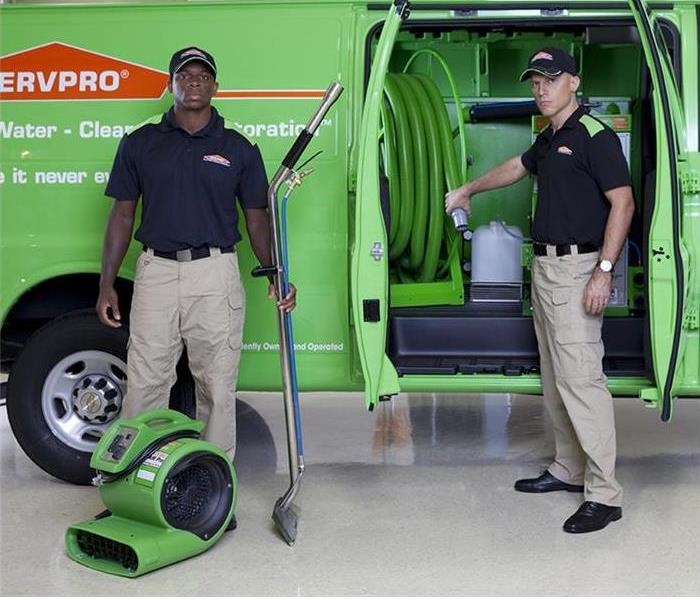 Two techs standing next to a SERVPRO Van